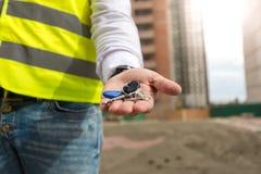 Zbliżenie młodzi architekta mienia klucze od nowego domu na ręce Zdjęcia Royalty Free