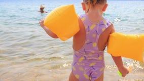 Zbliżenie mała dziewczynka w Zbawczych Armbands Iść Matkować w morzu zdjęcie wideo
