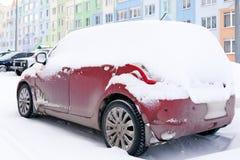 Zbliżenie małej czerwieni brudny samochód zakrywający z śniegów stojakami przeciw tło barwiącemu domowi Boczny widok Pojęcie śnie zdjęcia stock