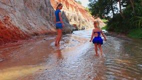 Zbliżenie macierzysta mała córka w błękitnym harcowaniu bosym w płytkim strumieniu zbiory wideo