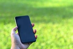 Zbliżenie man& x27; s ręka trzyma mądrze telefon z pustym miejscem s i używa zdjęcia stock