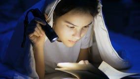 Zbliżenie materiał filmowy nastoletniej dziewczyny czytelnicza książka pod koc z latarką zbiory wideo