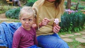 Zbliżenie matka Karmi z Łyżkową małą dziewczynką przeciw kwiatom zbiory