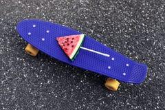 Zbliżenie mody błękitny deskorolka z arbuza popsicle na kiju, textured tło asfalt obrazy stock