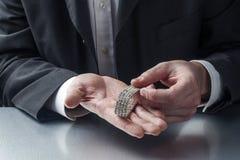 Zbliżenie na biznesmenie wręcza wystawiać cennego metalu klejnot dla pojęcia złoto i pieniądze w rękach Obraz Stock