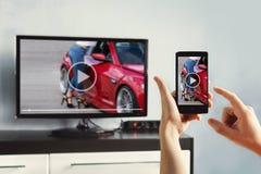 Zbliżenie na kobiety ręki mienia smartphone i używa app z pilot do tv Obraz Royalty Free