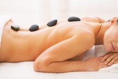 Zbliżenie na młodej kobiecie otrzymywa gorącego kamiennego masaż obrazy royalty free