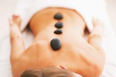 Zbliżenie na młodej kobiecie otrzymywa gorącego kamiennego masaż zdjęcie royalty free