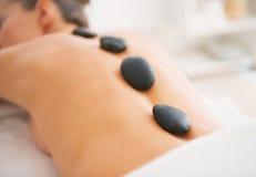 Zbliżenie na młodej kobiecie otrzymywa gorącego kamiennego masaż. tylni widok zdjęcia stock