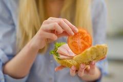 Zbliżenie na młodej kobiecie robi kanapce w kuchni obraz royalty free