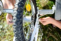 Zbliżenie na rękach męski naprawianie mechanizm bicykl, zielony tło outside Fotografia Royalty Free