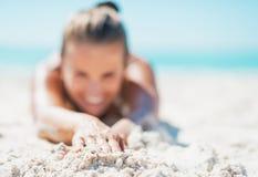 Zbliżenie na szczęśliwej młodej kobiecie kłaść na piaskowatej plaży w swimsuit Fotografia Royalty Free