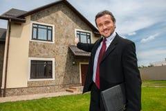 Zbliżenie na uśmiechniętym agencie nieruchomości przygotowywającym sprzedawać dom Zdjęcie Stock