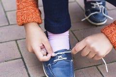 Zbliżenie nastoletnia dziewczyna wręcza wiązać shoelaces Obrazy Royalty Free