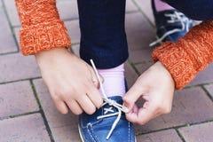 Zbliżenie nastoletnia dziewczyna wręcza wiązać shoelaces Fotografia Stock