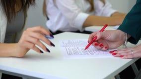 Zbliżenie nauczyciela cheks, kontrolna szkoły wyższej dziewczyny ucznia wiedza i umiejętności w notatniku w sali lekcyjnej zbiory wideo