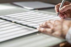 Zbliżenie niskiego kąta widok podpisuje dokument lub kontrakt mężczyzna zdjęcie stock