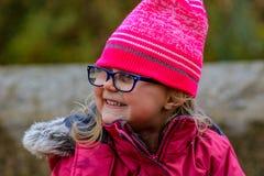 Zbliżenie obracał portret mała dziewczynka w popielatej kurtce z futerkowym kołnierzem i trykotowym kapeluszem w śnieżnym parku obraz stock