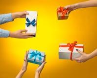 Zbliżenie obrazek mężczyzna i kobiety ` s ręki z prezenta pudełkiem Obrazy Stock
