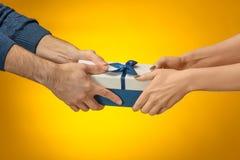 Zbliżenie obrazek mężczyzna i kobiety ` s ręki z prezenta pudełkiem Fotografia Stock