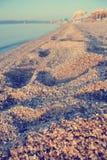 Zbliżenie odciski stopy na żwirowatej plaży w lecie; zatarty, retro styl, Obrazy Stock