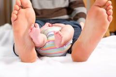 Zbliżenie ogromni cieki ojciec i mały nowonarodzony dziecko Duzi cieki dorosłe i malutkie nogi dziecko Szczęśliwy rodzicielstwo obrazy stock