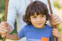 Zbliżenie ojciec pcha ślicznej chłopiec na huśtawce obrazy royalty free