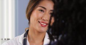 Zbliżenie ono uśmiecha się przy pacjentem azjata lekarka Zdjęcie Royalty Free