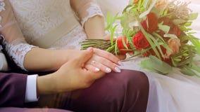 Zbliżenie państwo młodzi jest siedzący rękę i trzymający Fornal trzyma panny młodej ` s rękę zbiory