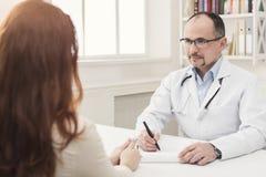 Zbliżenie pacjent i lekarka bierze notatki zdjęcie royalty free