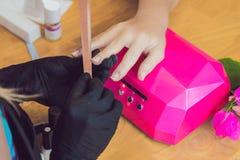 Zbliżenie palca gwoździa opieka manicure'u specjalistą w piękno salonie Manicurzysta farb gwoździe z gwoździa połyskiem zdjęcie royalty free