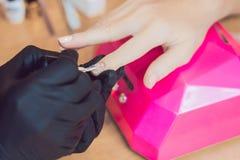 Zbliżenie palca gwoździa opieka manicure'u specjalistą w piękno salonie Manicurzysta farb gwoździe z gwoździa połyskiem obraz stock