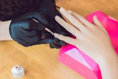 Zbliżenie palca gwoździa opieka manicure'u specjalistą w piękno salonie Manicurzysta farb gwoździe z gwoździa połyskiem fotografia royalty free