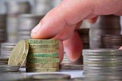 Zbliżenie palca wskazującego klepnięcia na stercie brytyjska funtowa moneta Obrazy Royalty Free