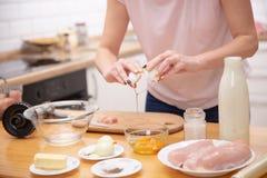Zbliżenie para ręki pęka jajko w szklanego puchar fotografia stock