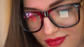 Zbliżenie patrzeje monitoru atrakcyjna młoda kobieta podczas gdy pracujący przy nowożytnym biurem i używać laptop, dziewczyny być zbiory