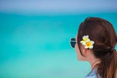 Zbliżenie piękna kobieta podczas tropikalnego plaża wakacje Cieszy się wakacje samotnie na plaży z frangipani kwiatami Fotografia Stock
