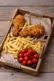 Zbliżenie pieczonego kurczaka nogi i francuzów dłoniaki z marynowanym tomat zdjęcia royalty free