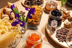 Zbliżenie piekarnia i przekąski, wysuszone owoc, kawałka parmesan ser, kwiaty, dokrętki, cynamonowi kije, rodzynki biscotti Pojęc obrazy royalty free