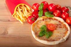 Zbliżenie pizzy withfrench smaży, pomidory, ser i basil na drewnianym tle, Zdjęcie Stock