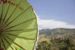 Zbliżenie pod antyk zieleni Asia parasolem na halnym tle fotografia stock
