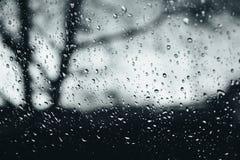 Zbliżenie podeszczowe kropelki na szklanym okno, wodne kropelki z lekkim odbiciem i refrakcja, zamazana ciemna jesień obraz royalty free