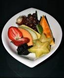 Zbliżenie pokaz asortowane pokrojone owoc na białym talerzu z czarnym tłem obraz stock