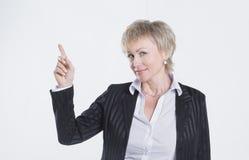 Zbliżenie pomyślna biznesowa kobieta wskazuje przy kopii przestrzenią zdjęcia stock
