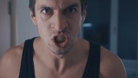 Zbliżenie portret agresywny mężczyzna w naganiacz krzyczącej i groźnej przemocy w domu zbiory