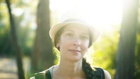 Zbliżenie portret atrakcyjna turystyczna dziewczyna uśmiechnięta i patrzeje w kamerę podczas gdy wycieczkujący pięknego las zbiory