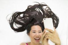 Zbliżenie portret azjatykcie kobiety kÅ'ama na ziemi z czarny dÅ'ugie wÅ'osy postÄ™pujÄ…cy wow i kursujÄ…cy telefon, zdjęcie royalty free