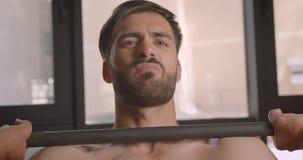 Zbliżenie portret bez koszuli mięśniowi caucasian mężczyzny udźwigu ciężary z wysiłek pozycją w gym indoors zdjęcie wideo