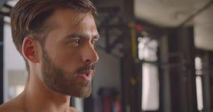 Zbliżenie portret bez koszuli mięśniowy caucasian mężczyzna opracowywa z dumbbells z wysiłek pozycją w gym indoors zdjęcie wideo