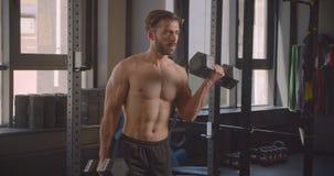 Zbliżenie portret bez koszuli mięśniowy caucasian mężczyzna opracowywa z dumbbells z wysiłek pozycją w gym indoors zbiory wideo